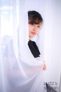 白ホリゾントで撮影したカーテン越しの女性のポートレート写真