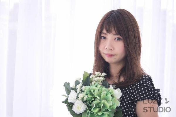 白ホリゾントで撮影した花を持っている女性のポートレート写真