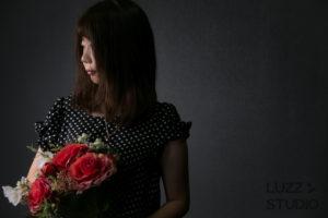 黒ホリゾントで撮影した花を持った女性のポートレート写真