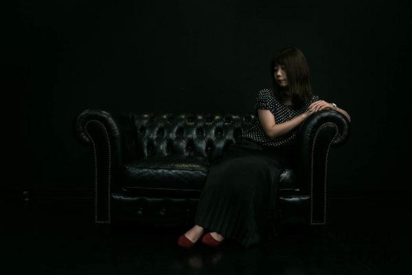 黒ホリゾントで撮影したソファでくつろぐ女性のポートレート写真
